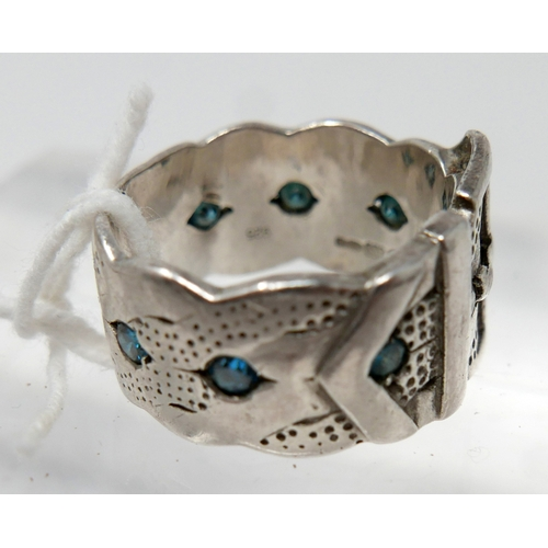 1096 - A Gentleman's sterling silver buckle-belt ring set with seven, round, faceted blue diamonds and text...