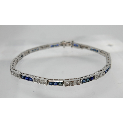 1006 - An 18ct white gold diamond and sapphire tennis bracelet, alternately set with thirty-two callibre-cu...