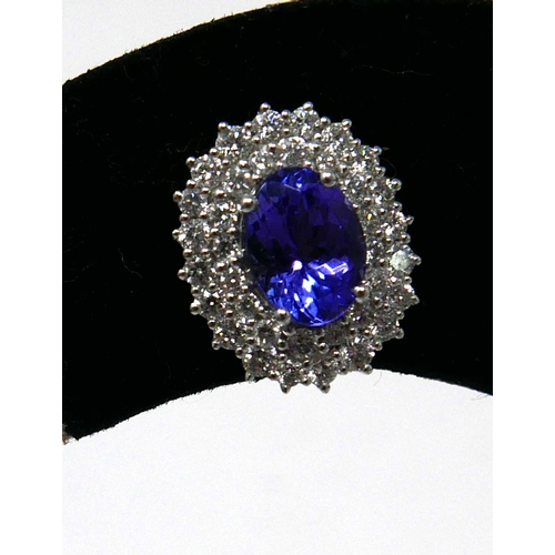 1129 - A pair of large, 18ct white gold diamond and tanzanite cluster earrings, the central oval tanzanite ...