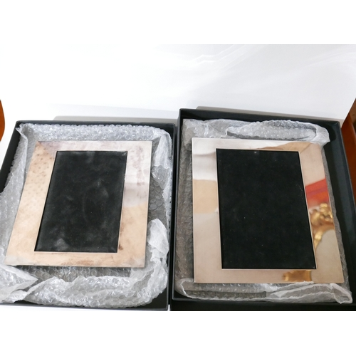 1213 - A pair of boxed, silver-plated photograph frames, 22 x 23cm and 20 x 21cm....