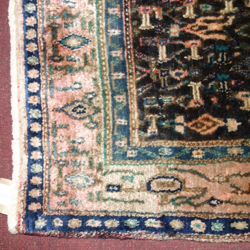 92 - A North West Persian Senneh rug, central diamond medallion with repeating petal motifs on a sapphire...