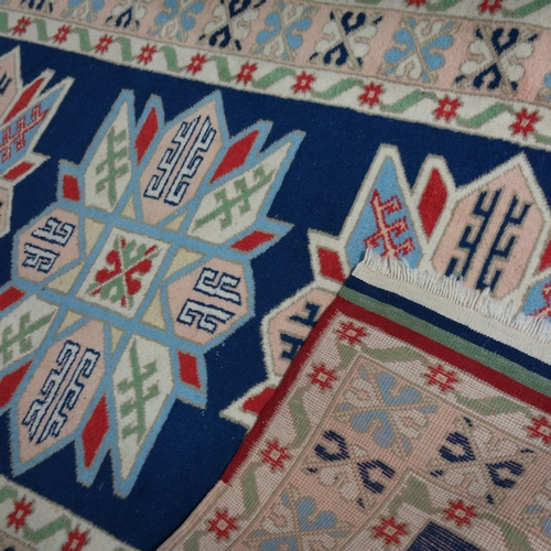 46 - A Kazak rug with triple geometric medallion, on a blue ground, contained by geometric border on a cr...