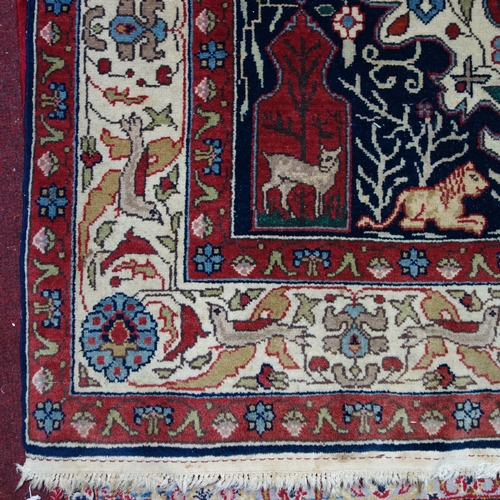 52 - A zoomorphic Tabriz carpet, with central floral medallion, on a red and blue ground, contained by fl...