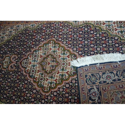 54 - A part silk Tabriz rug, with floral medallion, on a blue and beige ground, contained by floral motif...