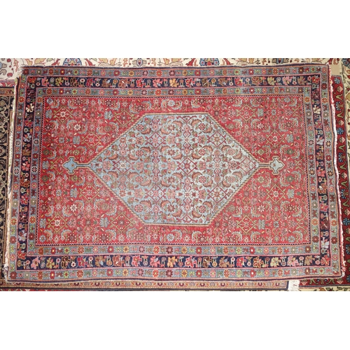 59 - A Bidjar rug, with central floral diamond medallion, on a blue ground, contained by geometric motifs...