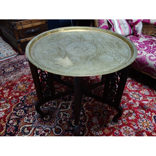 6 - An Islamic brass tray on folding hardwood stand, the tray engraved with scrolling foliage, geometric...