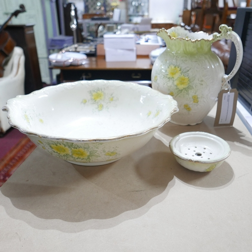 247 - A 19th century Carlton Ware ivory porcelain jug and wash bowl with floral decoration...