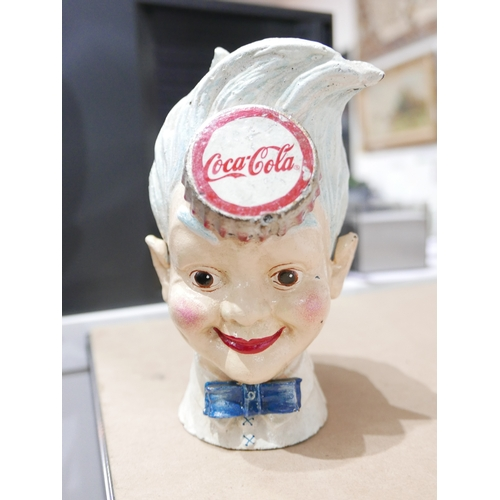 35 - A collection of Coca-Cola memorabilia, to include a cast iron money bank in the form of young boy's ...