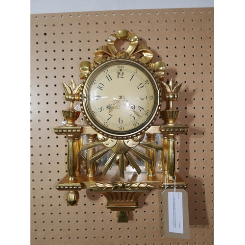 5 - A gilt wall clock in the Neo Classical taste, the round convex dial with Arabic numerals, the case w...