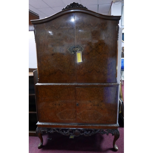 143 - A mid 20th century burr walnut drinks cabinet with well fitted and mirrored interior, makers label, ...