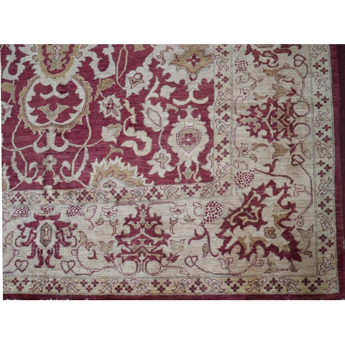 60 - A large Afghan Chubi carpet, with stylized floral design on a rouge and beige ground, bought from Se...