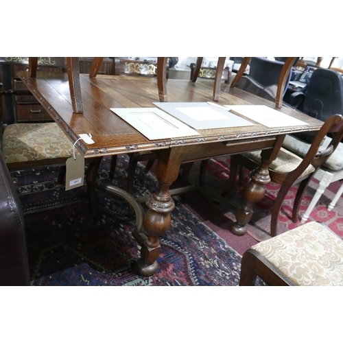 201 - WITHDRAWN- An early 20th century oak draw leaf table, raised on turned baluster supports and bun fee...