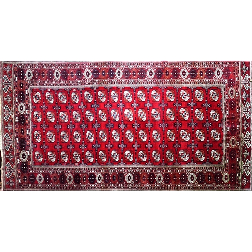 67 - A North East Persian Turkoman carpet, repeating all over gul motifs on a rouge field within stylised...