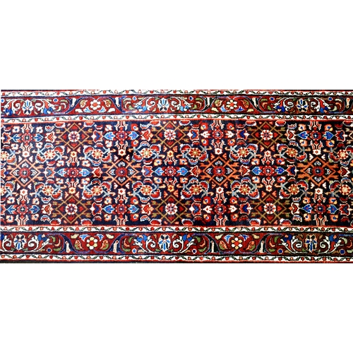 69 - A North West Persian Farahan runner, repeating stylised petal motifs on a sapphire field complimente...