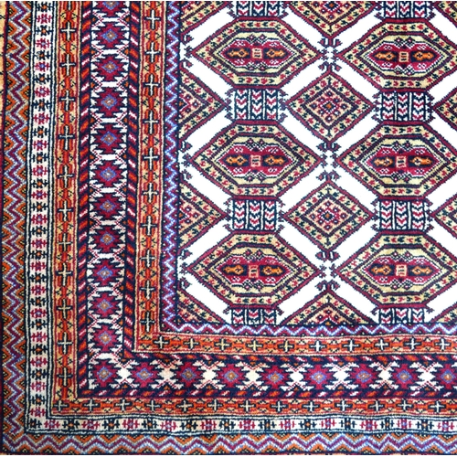 73 - A North East Persian Turkoman rug, repeating stylised gul motifs on an ivory field within stylised g...