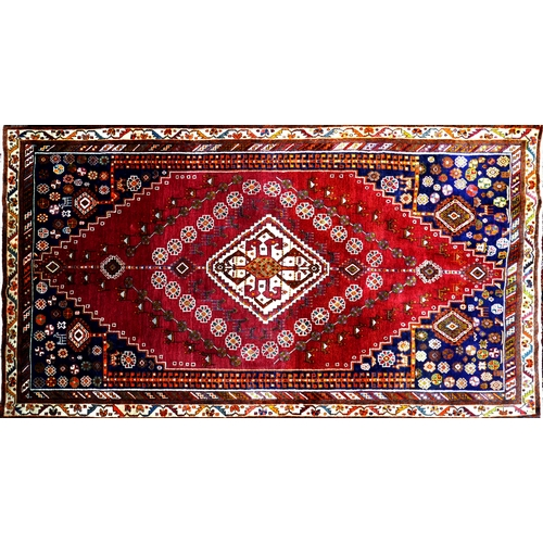 81 - A South West Persian Qashgai carpet, central diamond medallion with repeating petal motifs on a terr...