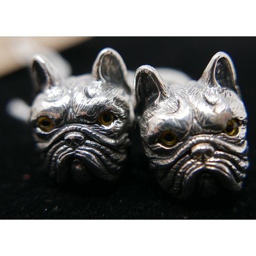 21 - A pair of sterling silver cufflinks in the form of bulldog-heads with collars set with small sapphir...
