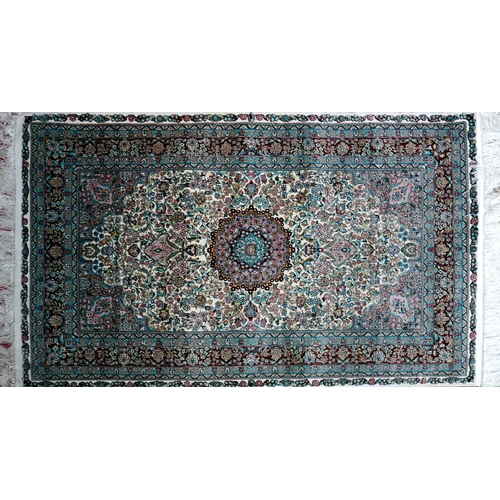 39 - A 20th century fine silk Turkish Hereke rug, with central floral medallion, on a green ground, conta...