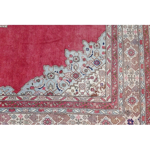 78 - A large Tabriz carpet with central floral medallion, on a red ground, contained by geometric floral ...