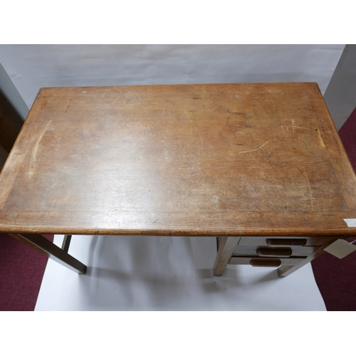 155 - An Edwardian oak desk with three drawers and brush slide, H.76 W.121 D.68cm...