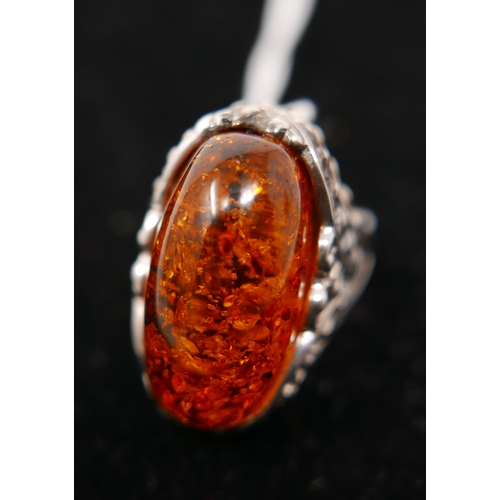194 - A large sterling silver and oval amber ring, the silver pierced mount in the form of detailed snowdr...