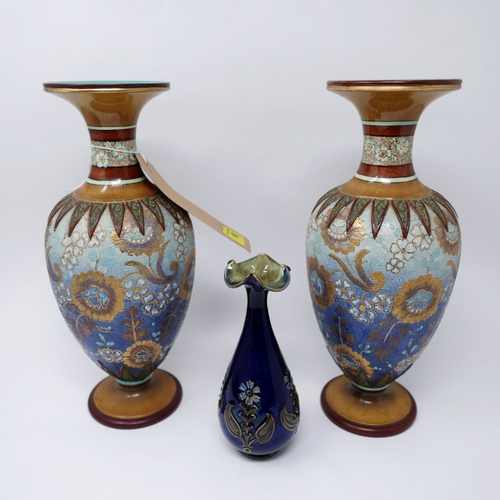 169 - A pair of Doulton Lambeth vases, polychrome decorated with stylised flowers, on circular bases, bear...