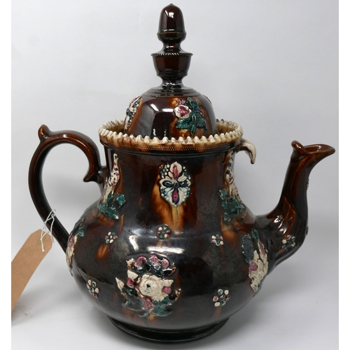 159 - A large brown glazed teapot, polychrome decorated with flowers, H.38cm...
