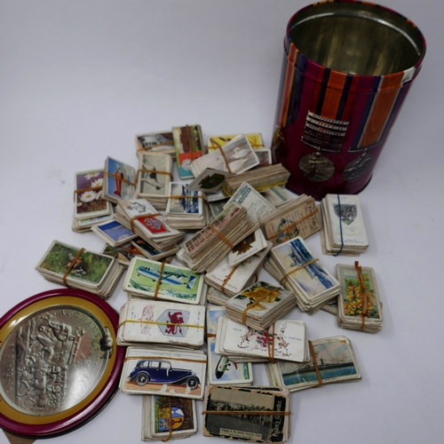 55 - A collection of vintage cigarette cards in cylindrical tin...
