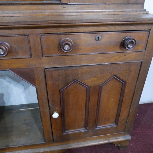 202 - An early 20th century oak dresser, four glazed doors above three drawers and two cupboard doors, rai...