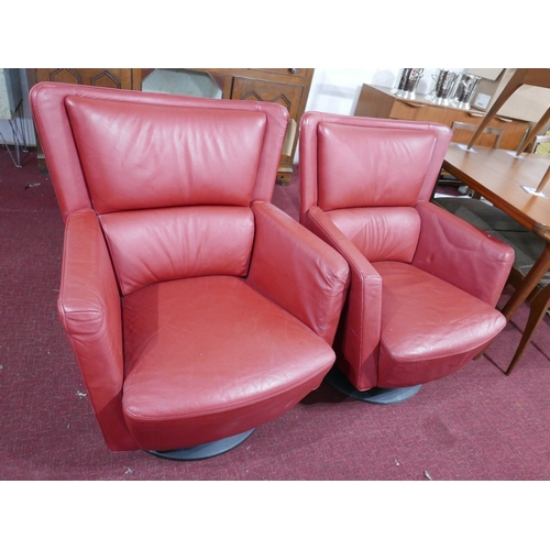 226 - A pair of Kinnarps red leather swivel chairs...