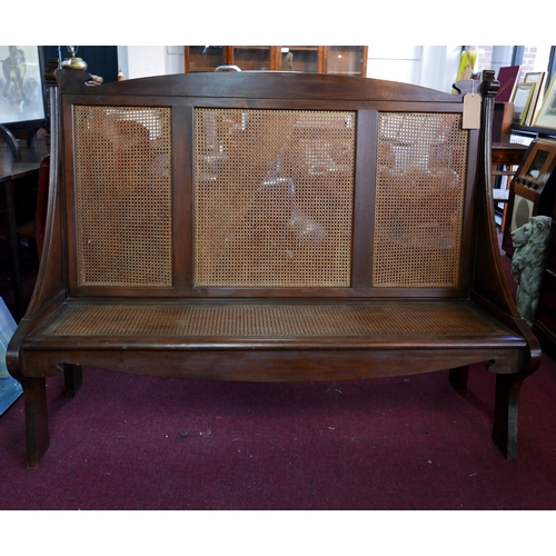 256 - An Arts & Crafts walnut settle with cane seat and backrest, H.118 W.151 D.54cm...