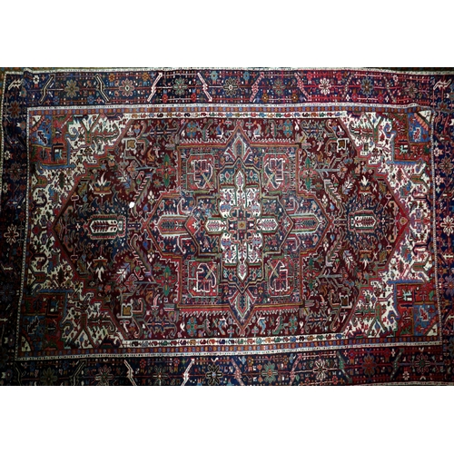 270 - An antique Heriz carpet, with central geometric medallion, on a red, blue and cream ground, containe...