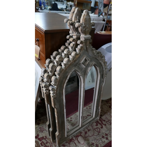 294 - Three Gothic style garden mirrors, distressed painted, with floral finial above twin arched glass pl...
