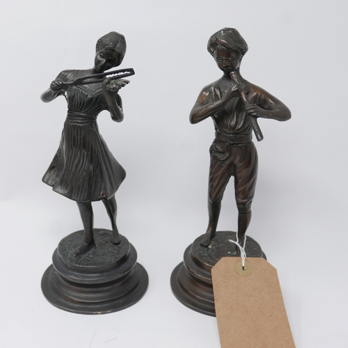 323 - Two cast bronze figures of a young man playing the flute and a young lady playing the violin, on ste...