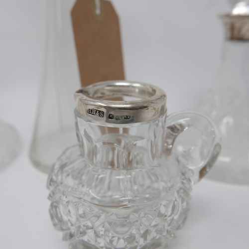 328 - A pair of small crystal decanters with silver collars, together with a silver mounted jug and white ...