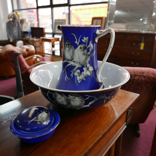 193 - A Burslem Midwinter blue glazed jug, bowl and soap dish, decorated with birds on branches and with g...