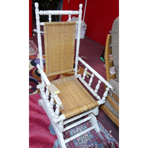 315 - A white painted rocking chair, with rattan backrest and seat, H.110cm...