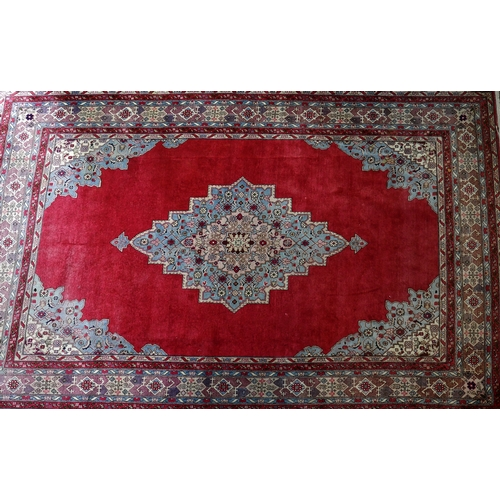387 - A large Tabriz carpet with central floral medallion on a red ground, contained by geometric floral b...