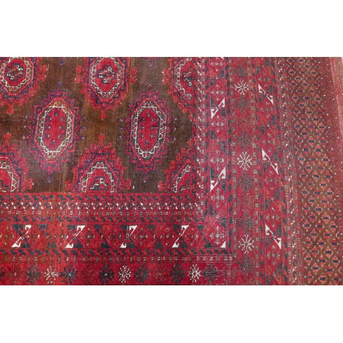 385 - A large Turkmen Bokhara carpet, with central repeating geometric motifs on a red ground, contained b...