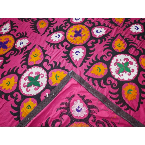 78 - An Uzbek Suzani rug, repeating stylised geometric motifs on a rouge field, 250 x 210cm...