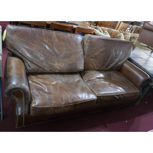 293 - A Howard style brown leather and stud bound sofa...