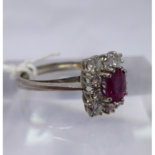 9 - An 18ct white gold, natural ruby and diamond cluster ring, the central oval faceted natural ruby in ...