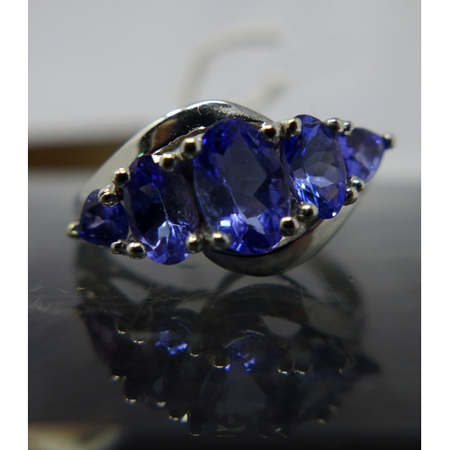21 - A boxed 14ct white gold tanzanite and diamond ring, set with five graduated oval faceted natural tan...