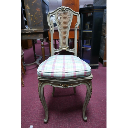 96 - A grey painted French chair, parcel gilded, with cane seat and back rest, raised on cabriole legs...