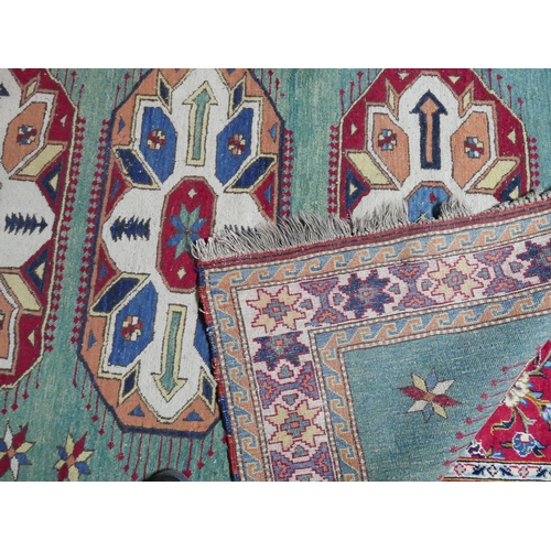 99 - An early 20th century Afghan rug with three geometric medallions on a green ground, contained by geo...