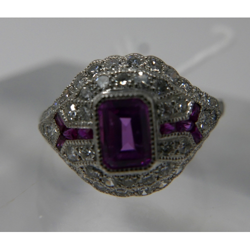 310 - An 18ct white gold Art Deco style diamond and ruby bombe shaped ring, centrally set with a rectangul...