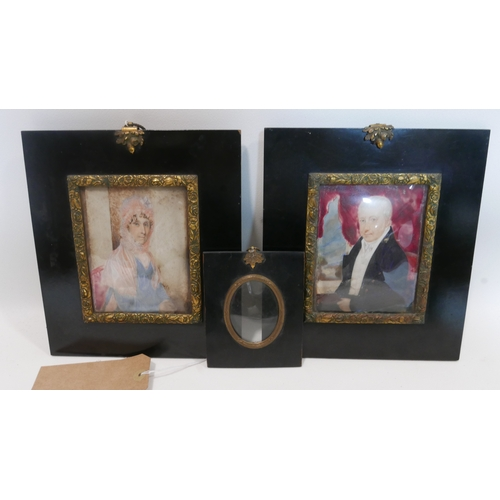 27 - A pair of 19th century miniature portraits on ivory of a lady and gentleman, in ebonised frames with...