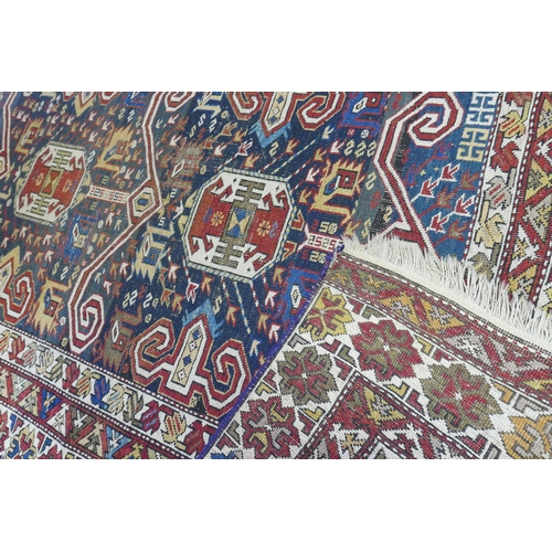 70 - An antique Perpadil rug with two geometric medallions, surrounded by geometric motifs, on a red and ...