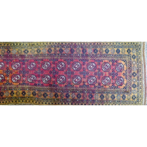 80 - A 20th century Afghan Bokhara runner, with repeating gull motifs, on a red and orange ground, contai...