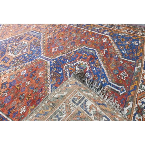 86 - An antique Shiraz carpet with triple geometric diamond medallions, on a blue and orange ground, cont...